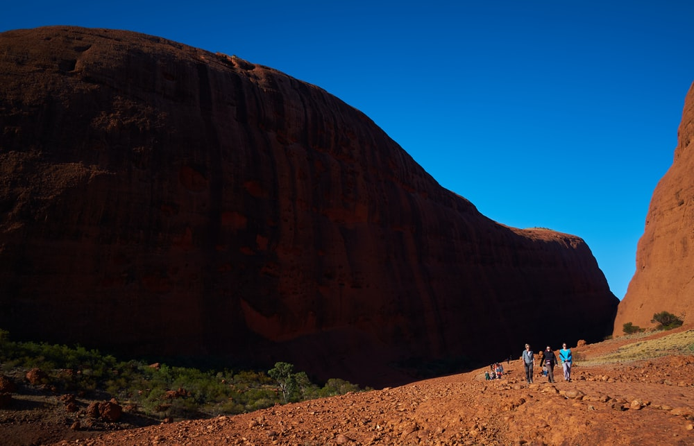 people standing on brown sand near brown rock formation during daytime