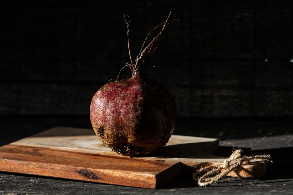 red and brown round fruit on brown wooden table