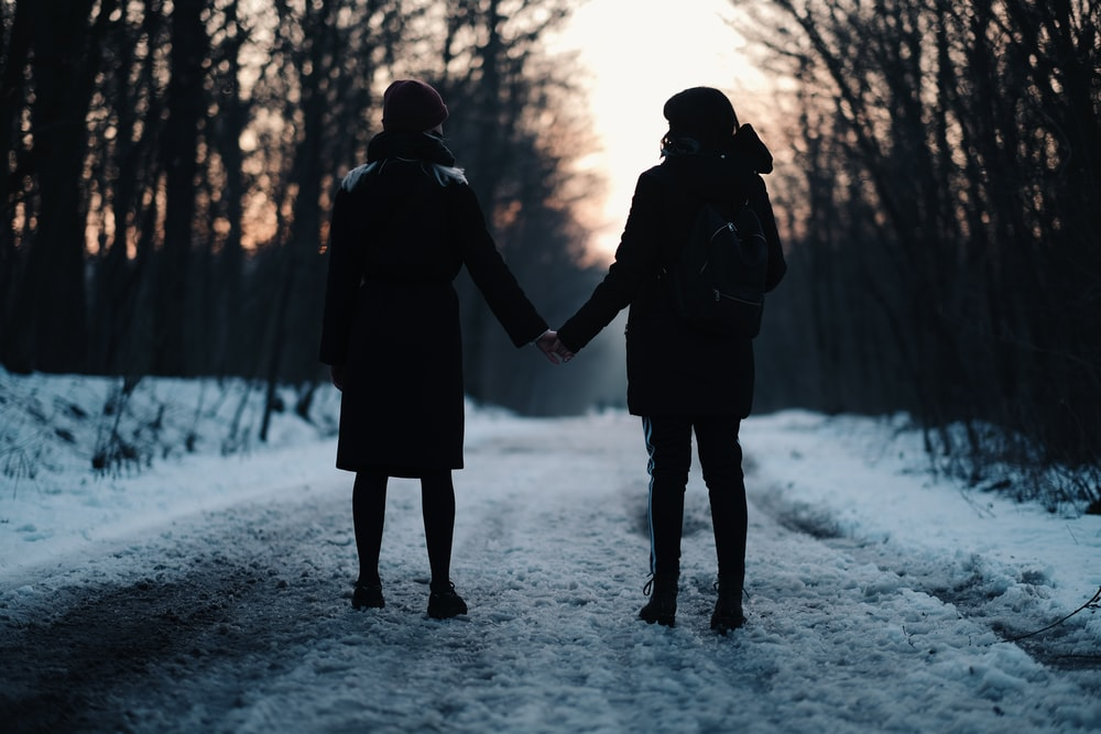 man and woman holding hands while walking on snow covered ground during daytime