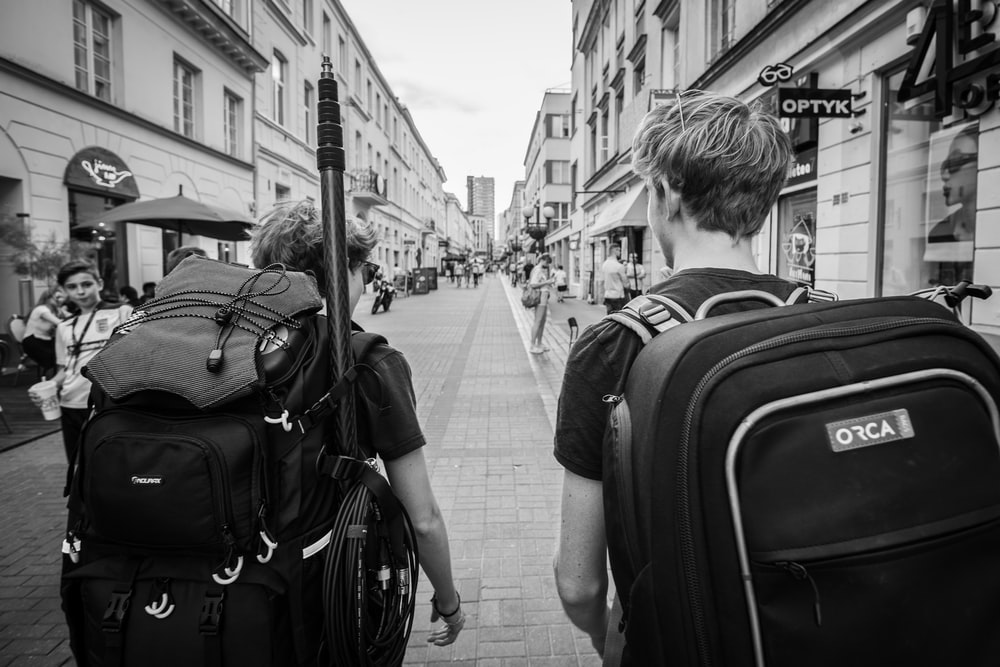 grayscale photo of man in black jacket carrying backpack walking on sidewalk