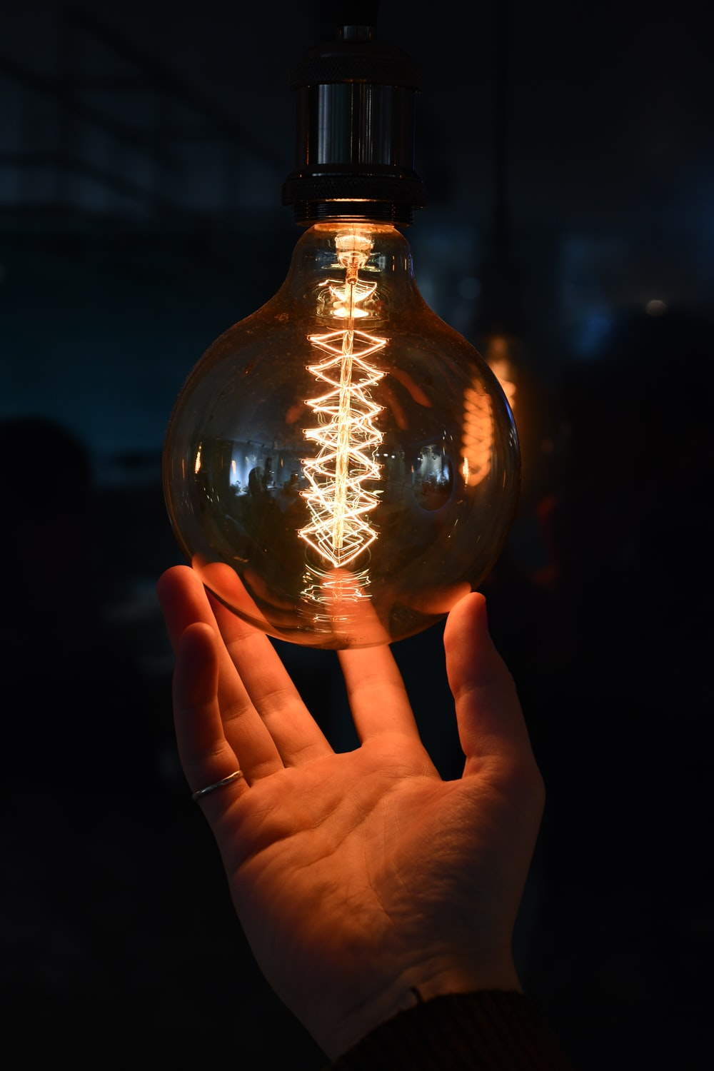 person holding clear glass bulb