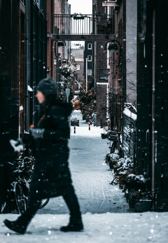 person in black jacket walking on street during daytime