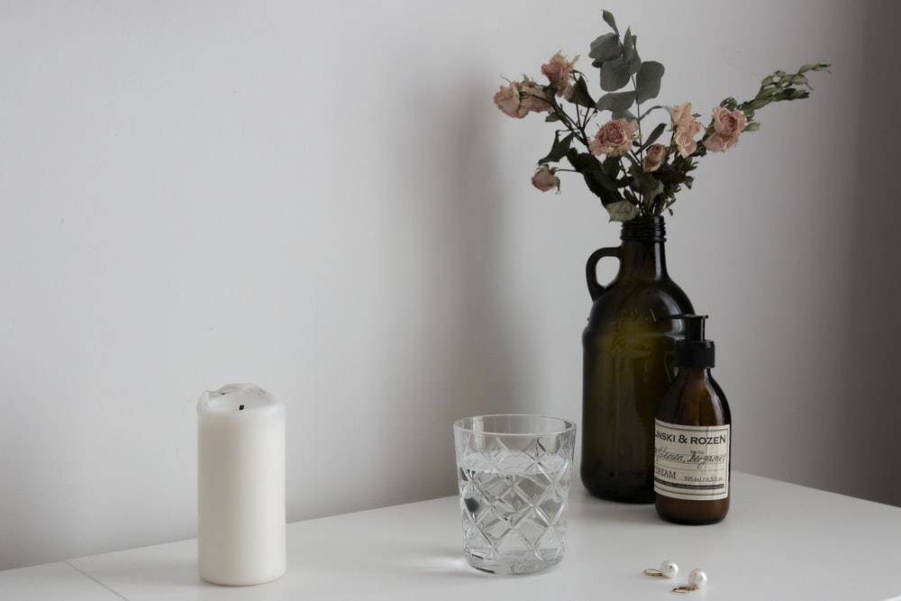 white pillar candle beside clear glass candle holder