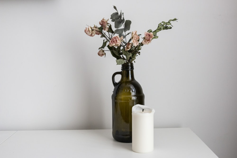 white flowers in brown glass vase