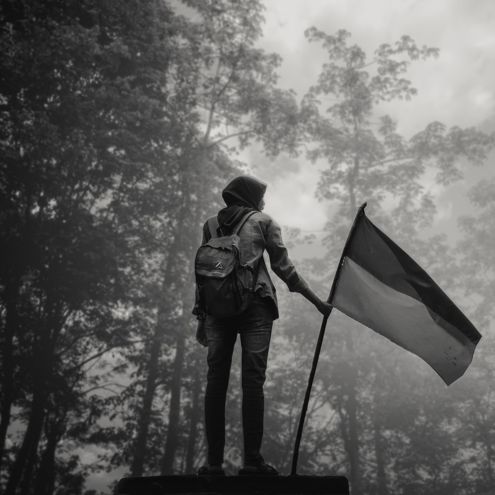man in black jacket holding yellow and green flag