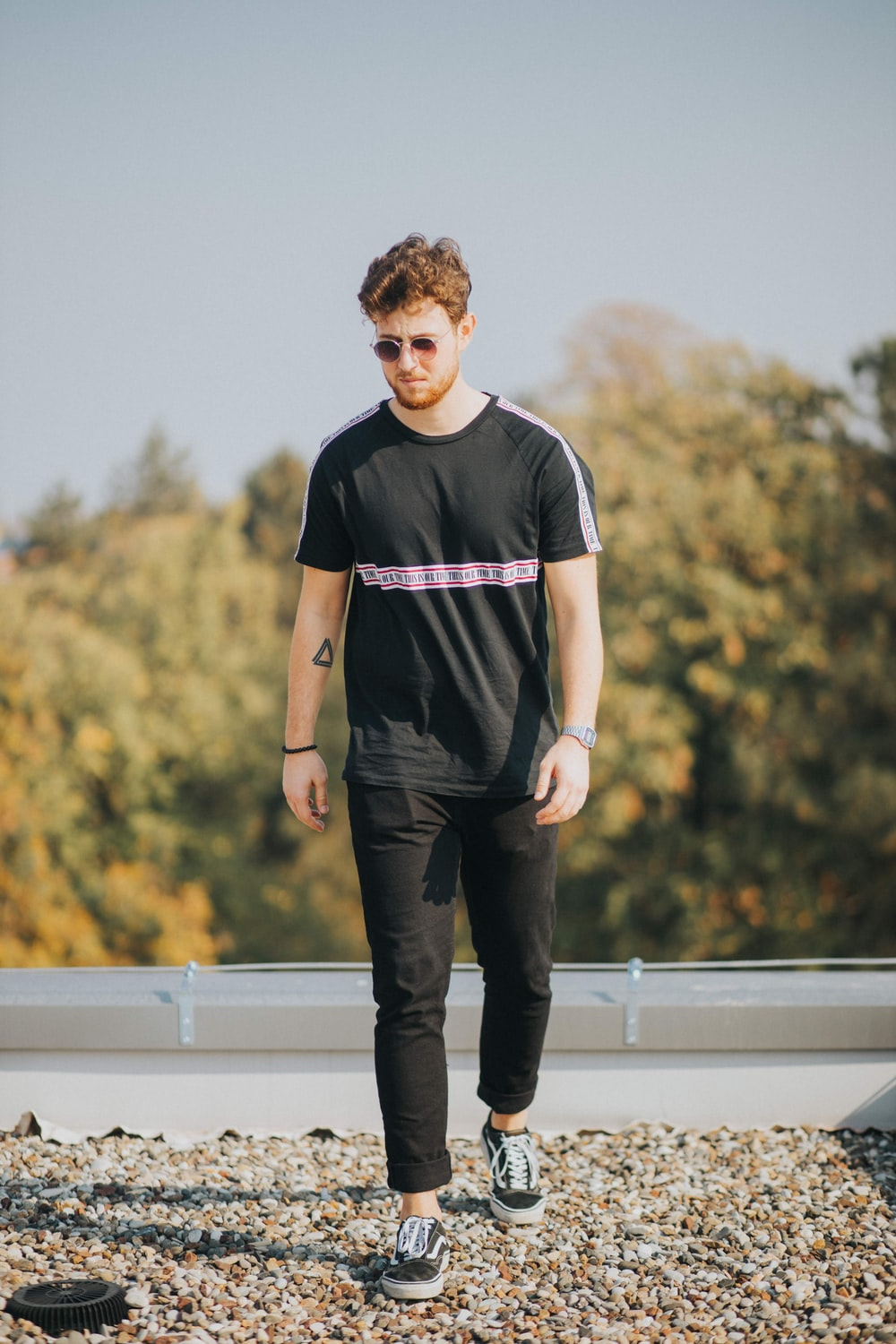 man in black and white adidas crew neck t-shirt and black pants standing on white