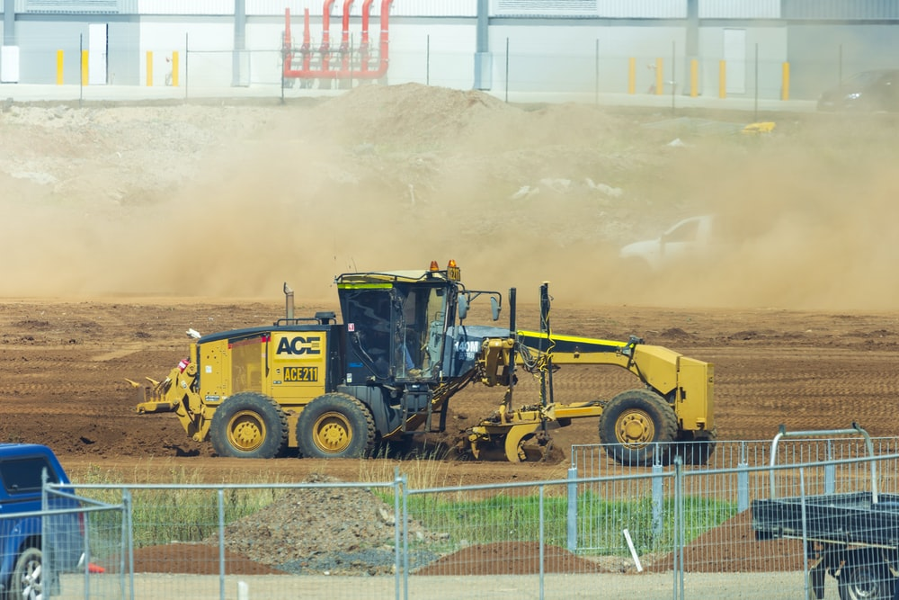 yellow and black heavy equipment on field during daytime