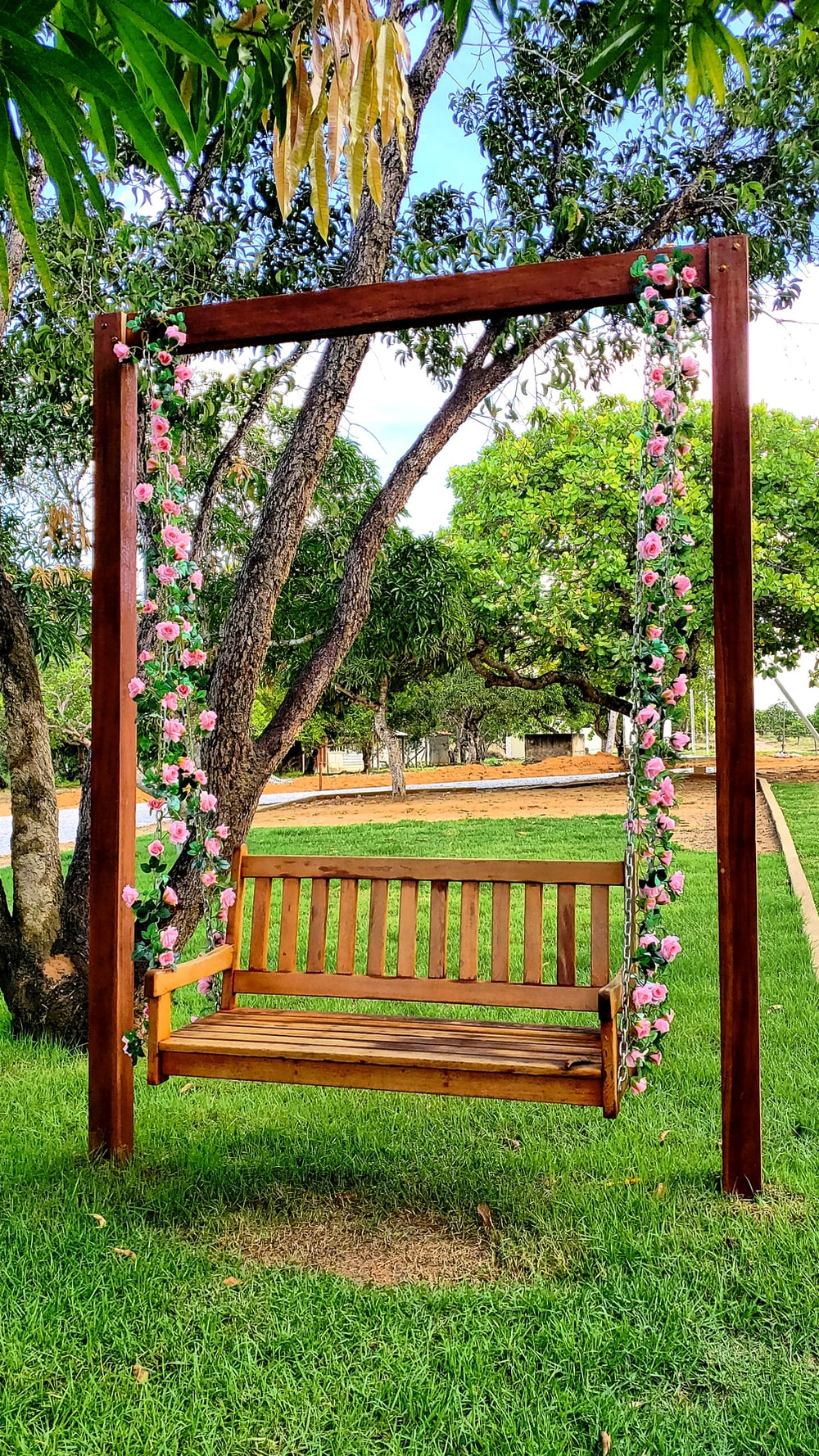 brown wooden bench under green and pink leaf tree
