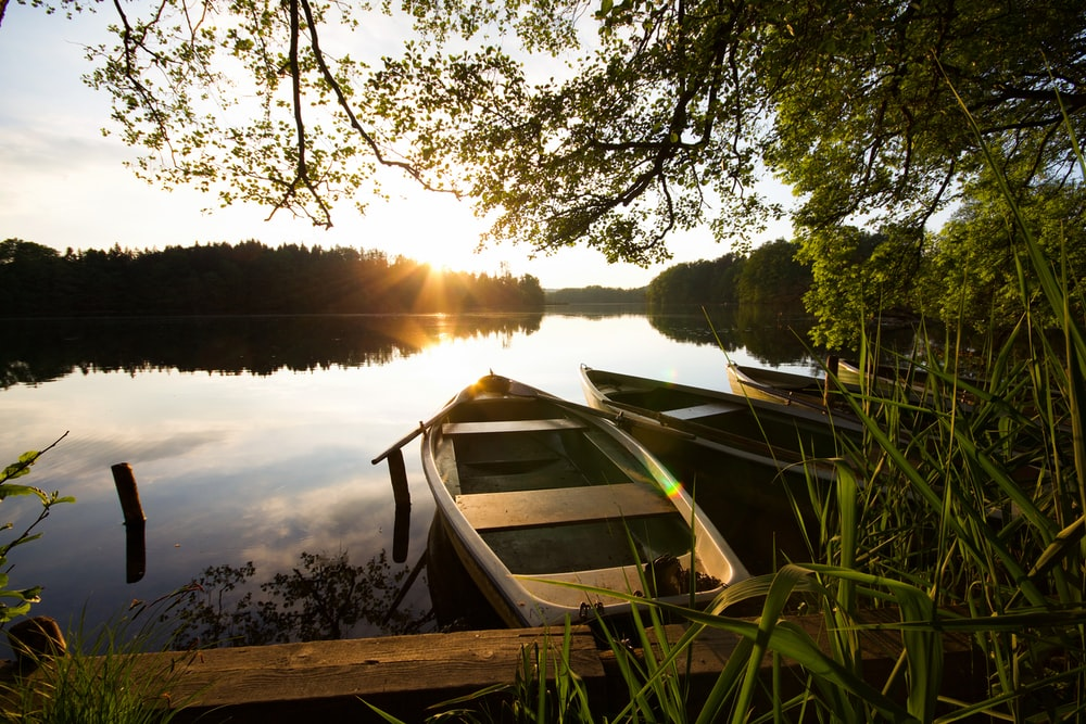 white and brown boat on lake during sunset