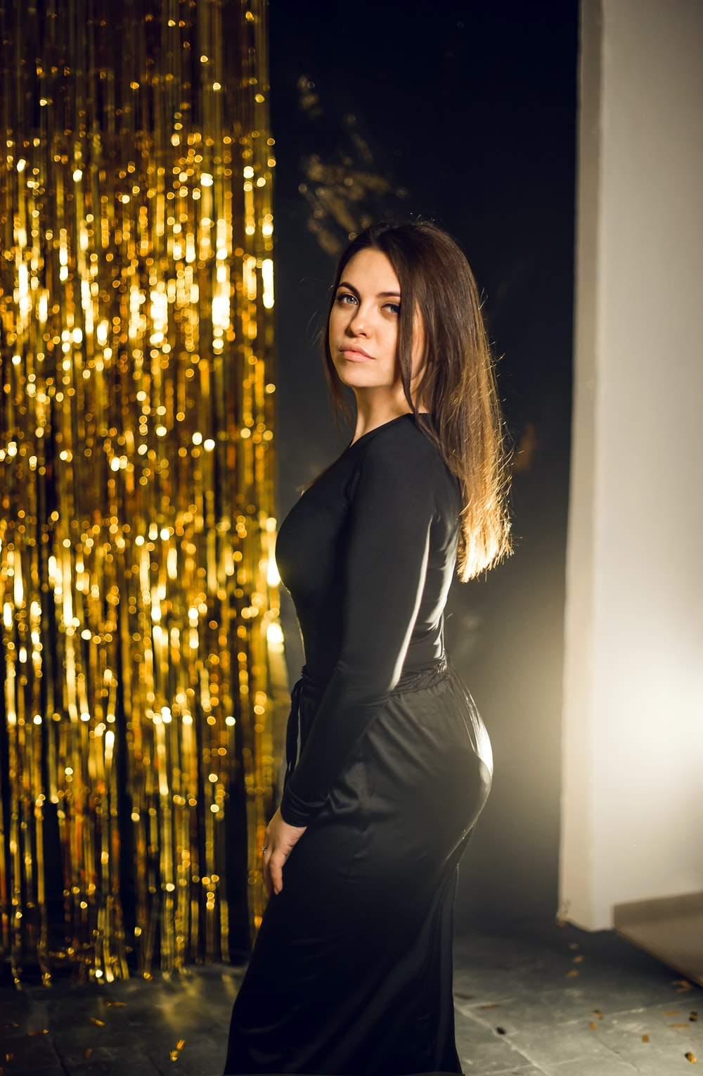 woman in black long sleeve dress standing beside brown string lights