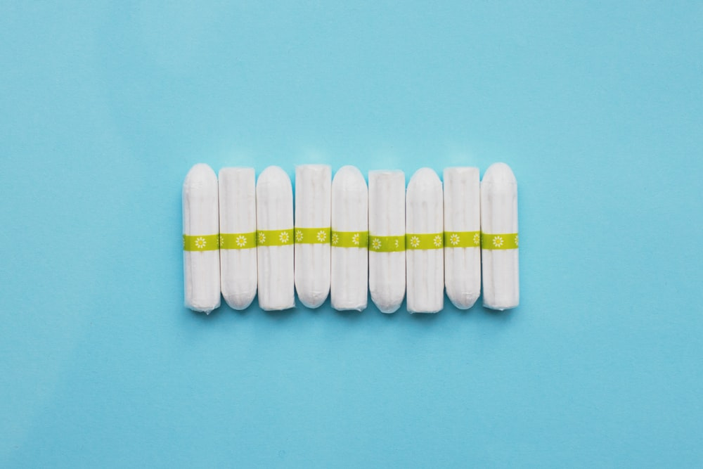 white oval medication pill on teal surface