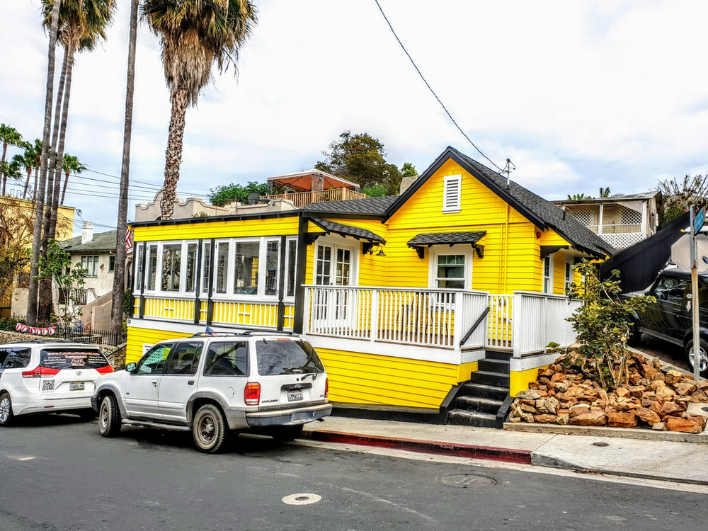 white suv parked beside yellow and green house during daytime