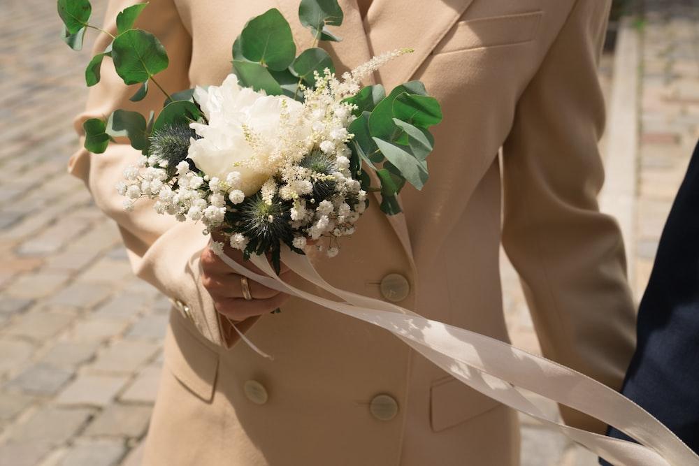 woman in beige blazer holding white flower bouquet