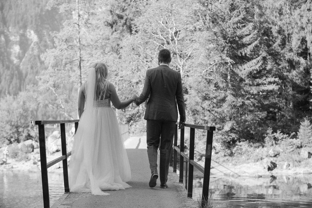 grayscale photo of man and woman standing on wooden dock