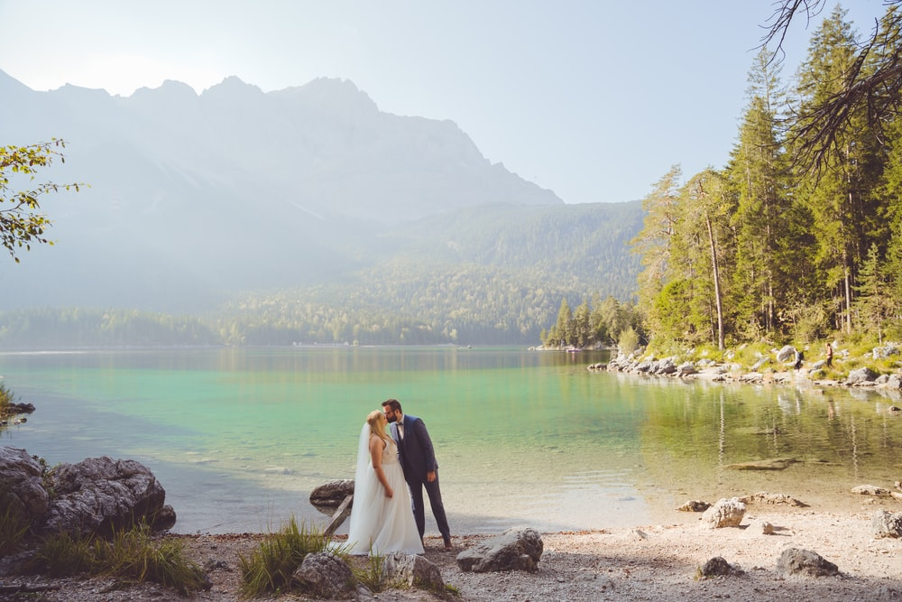 bride and groom standing on brown sand near body of water during daytime