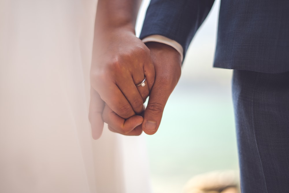 man in black suit jacket holding hands with woman in white dress