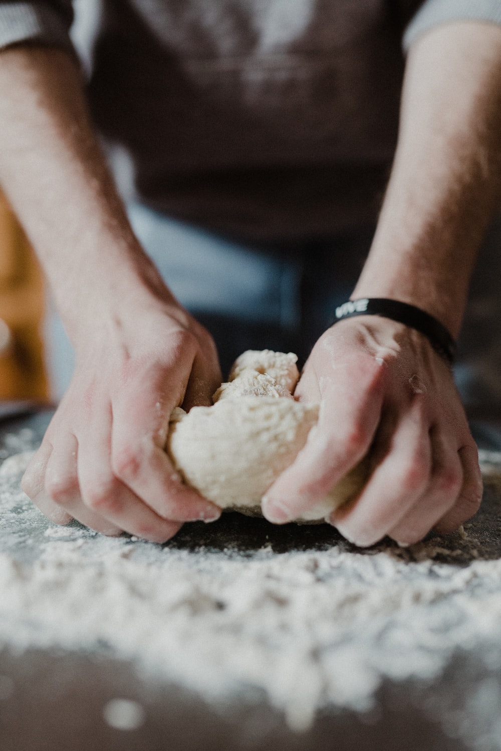 person holding white dough on brown wooden table