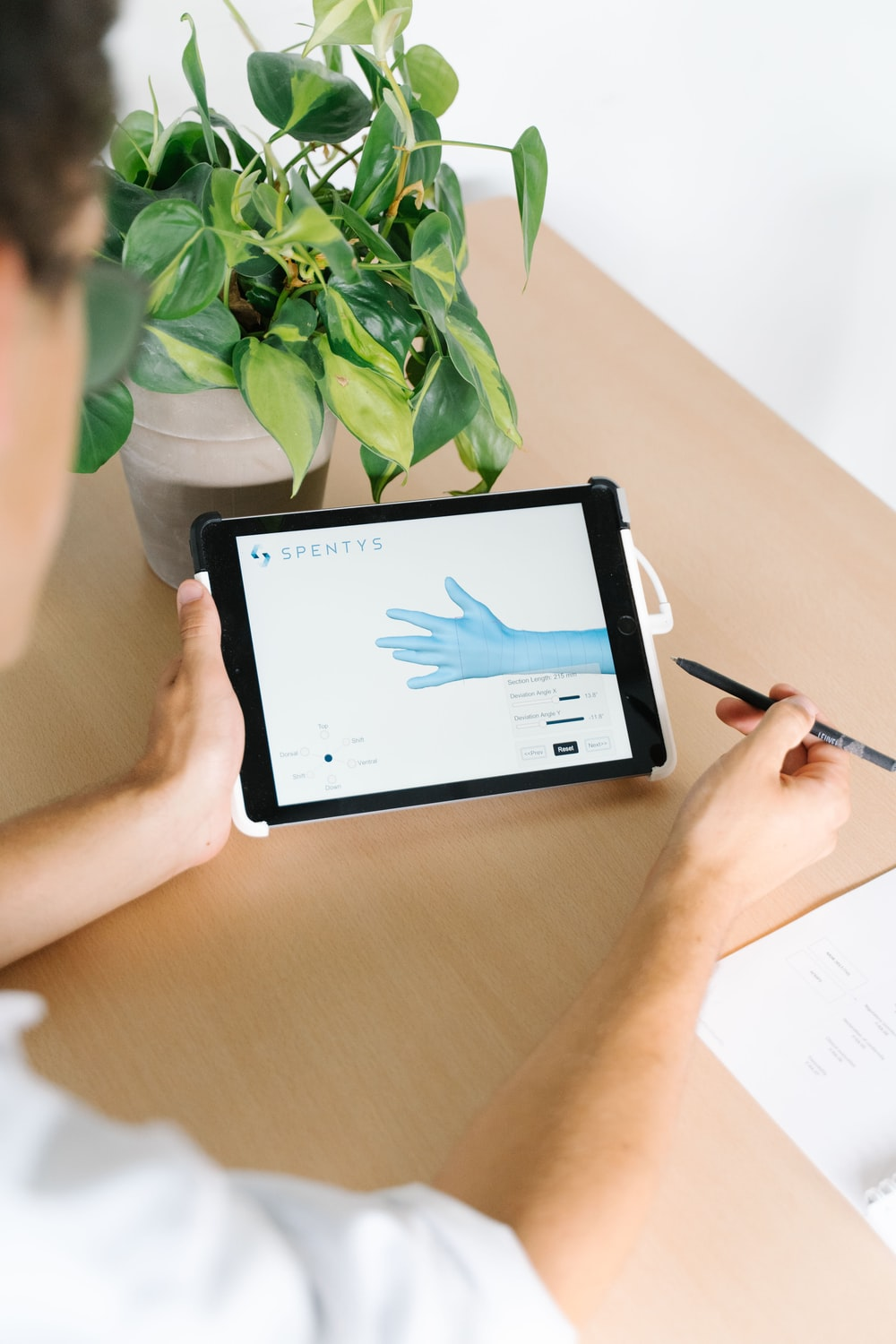 person holding black ipad on brown wooden table