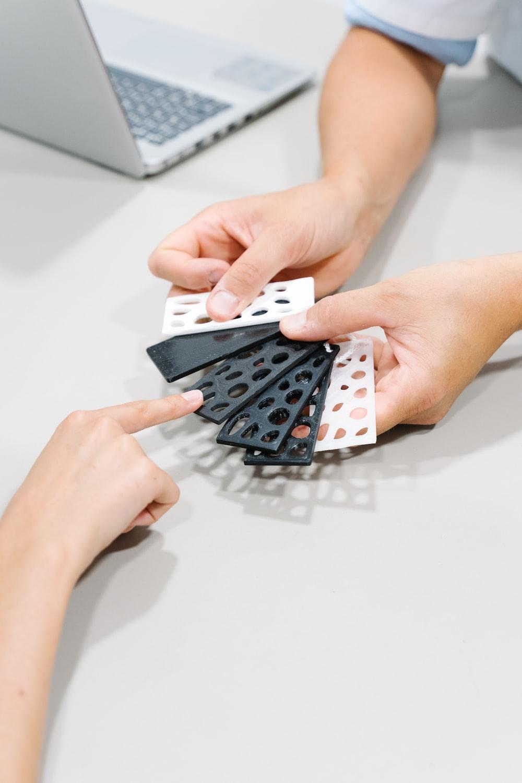 person holding black and white polka dot print textile