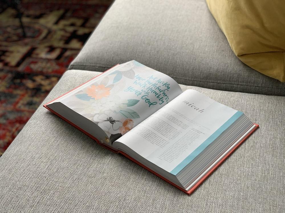 white book on gray textile