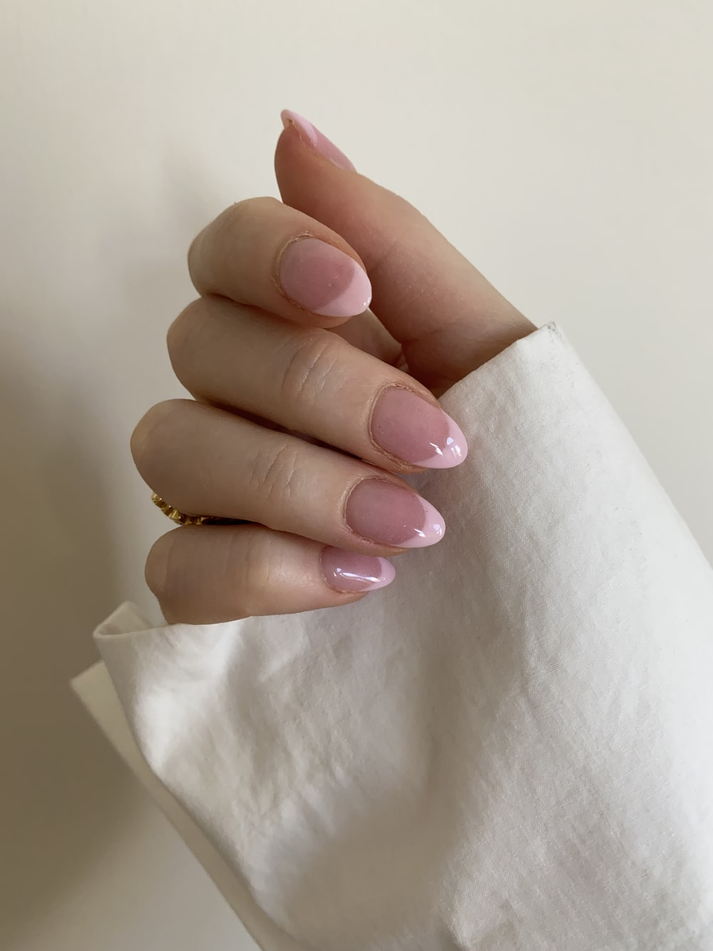 person with pink manicure on white textile