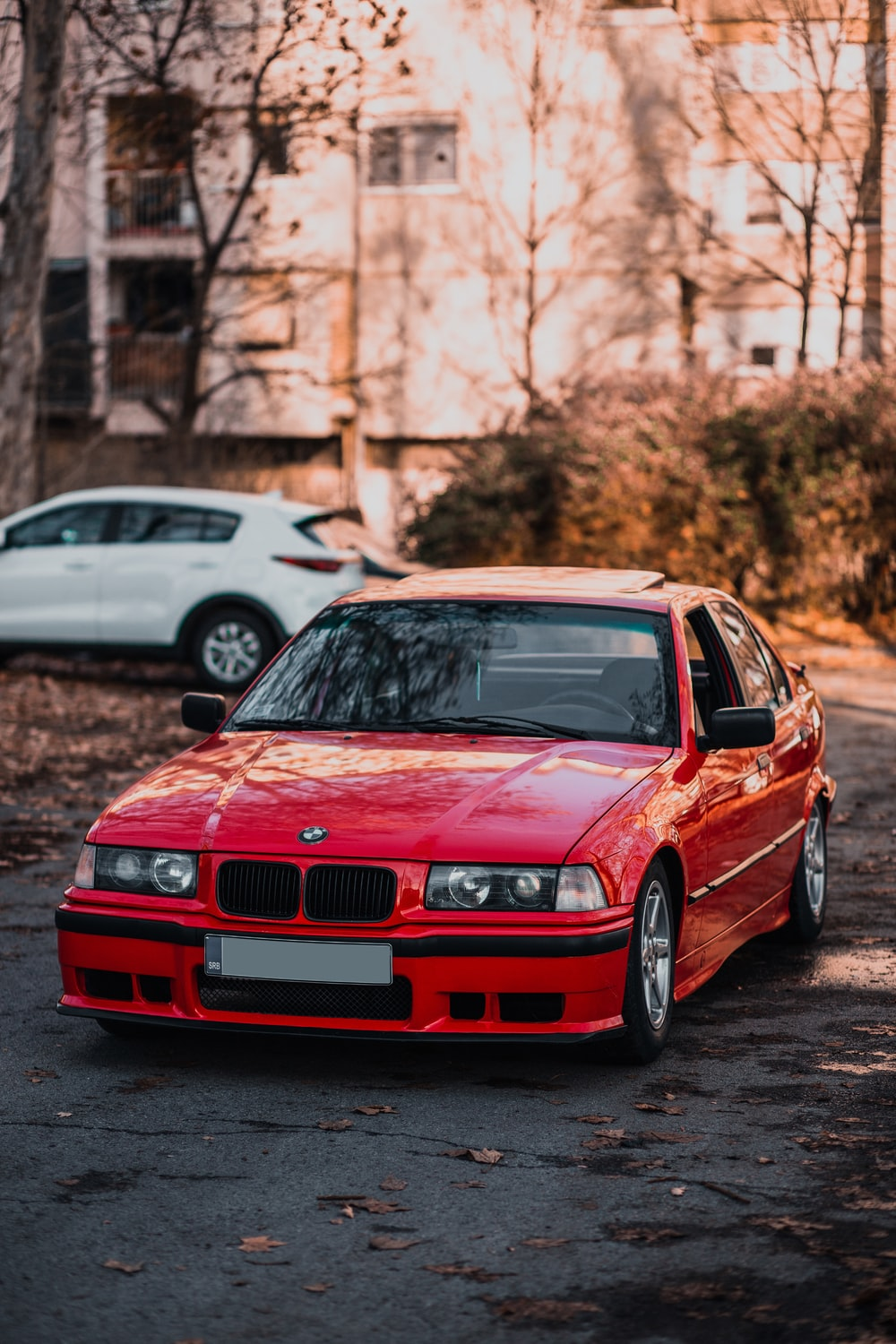 red bmw m 3 parked on street during daytime