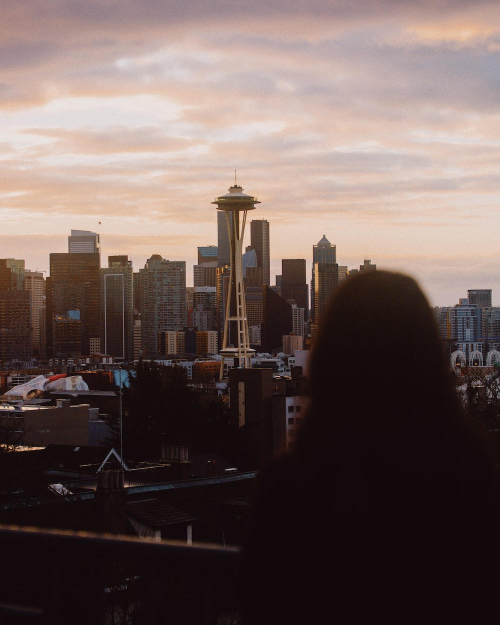 woman in black jacket standing on top of building during sunset