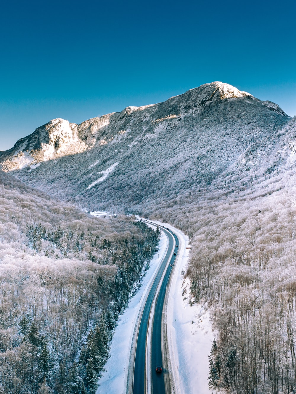 snow covered road near mountain under blue sky during daytime