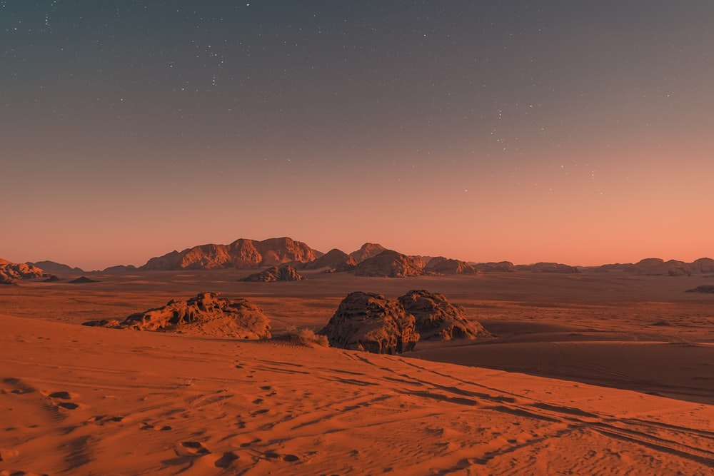 brown sand under blue sky during night time