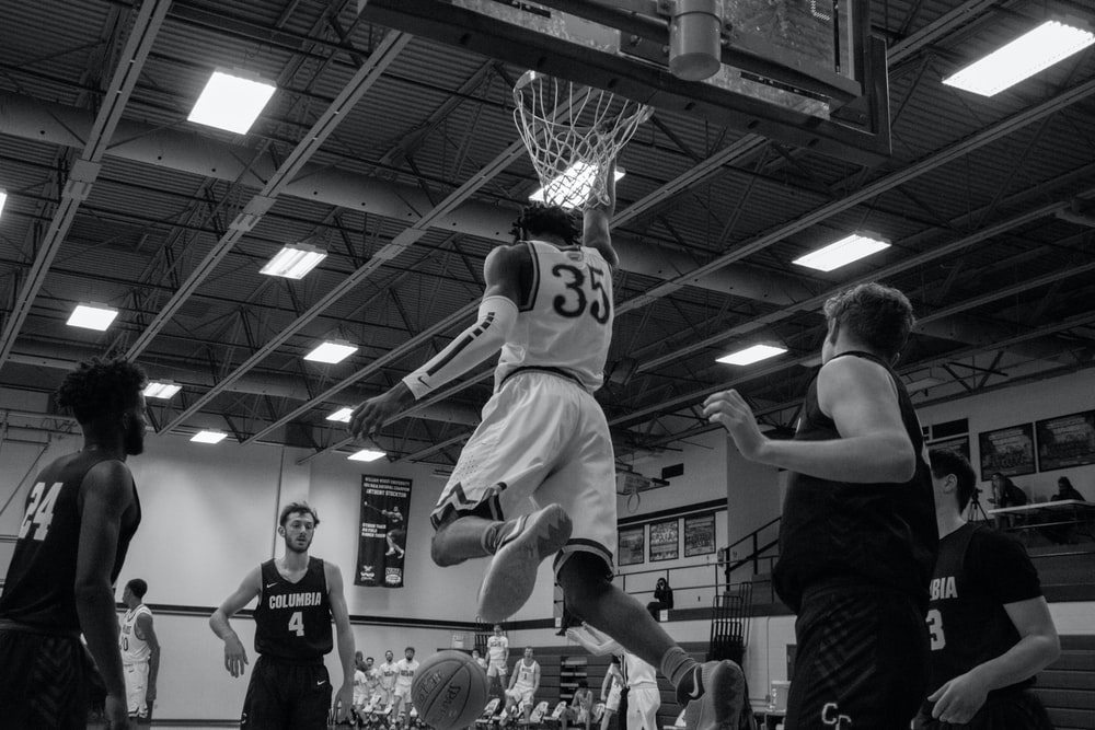 grayscale photo of basketball players playing basketball