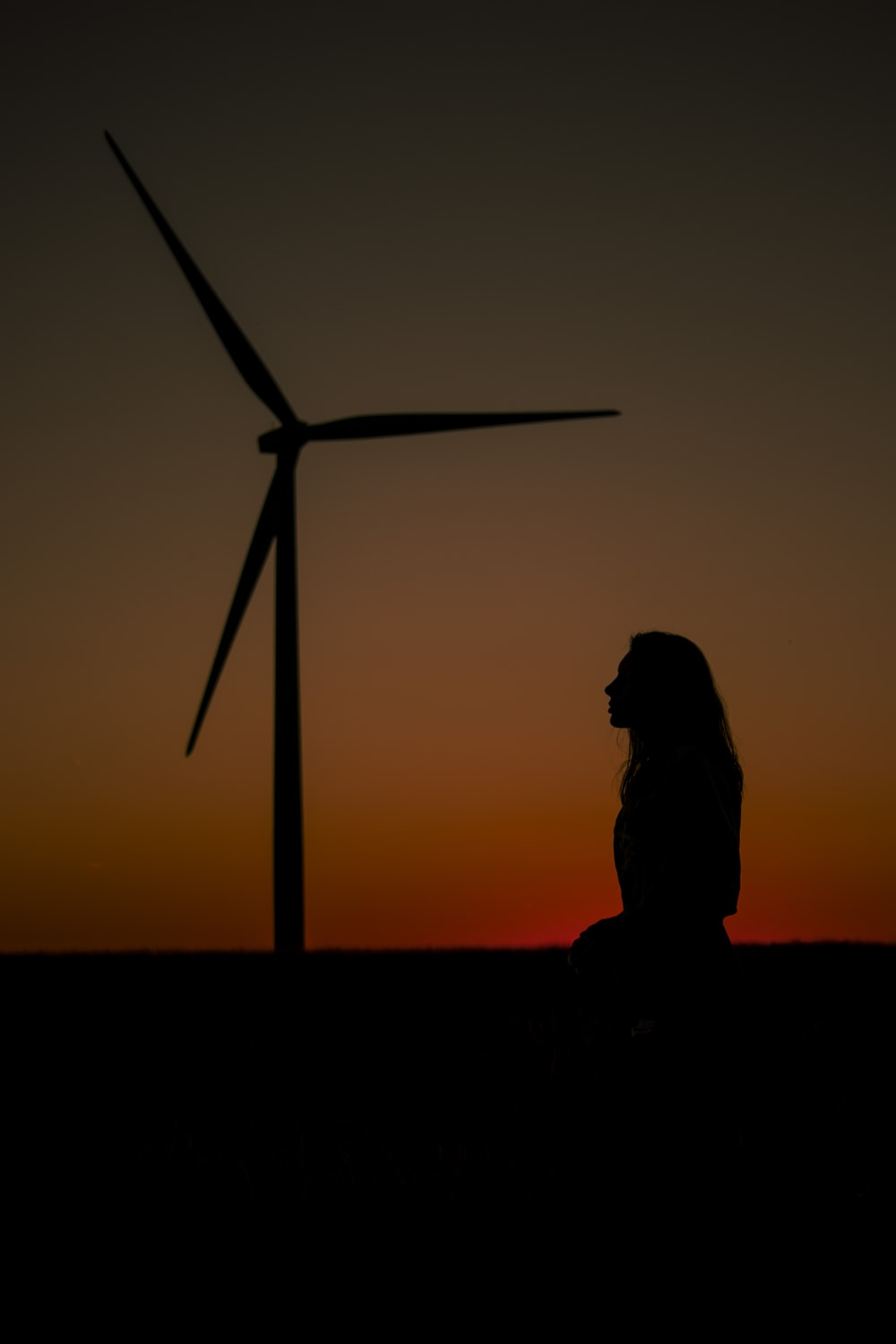 silhouette of person standing near windmill during sunset