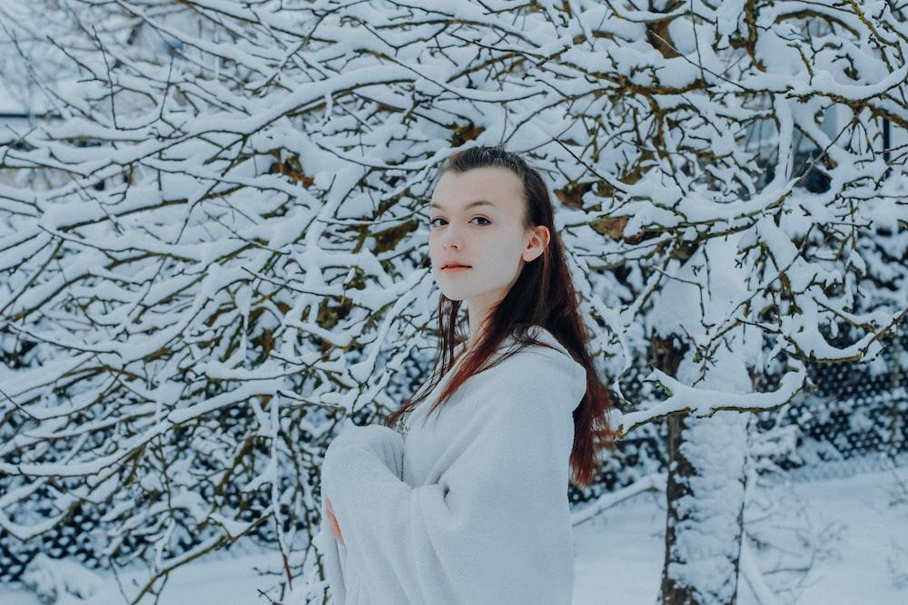 woman in white long sleeve shirt standing near white tree