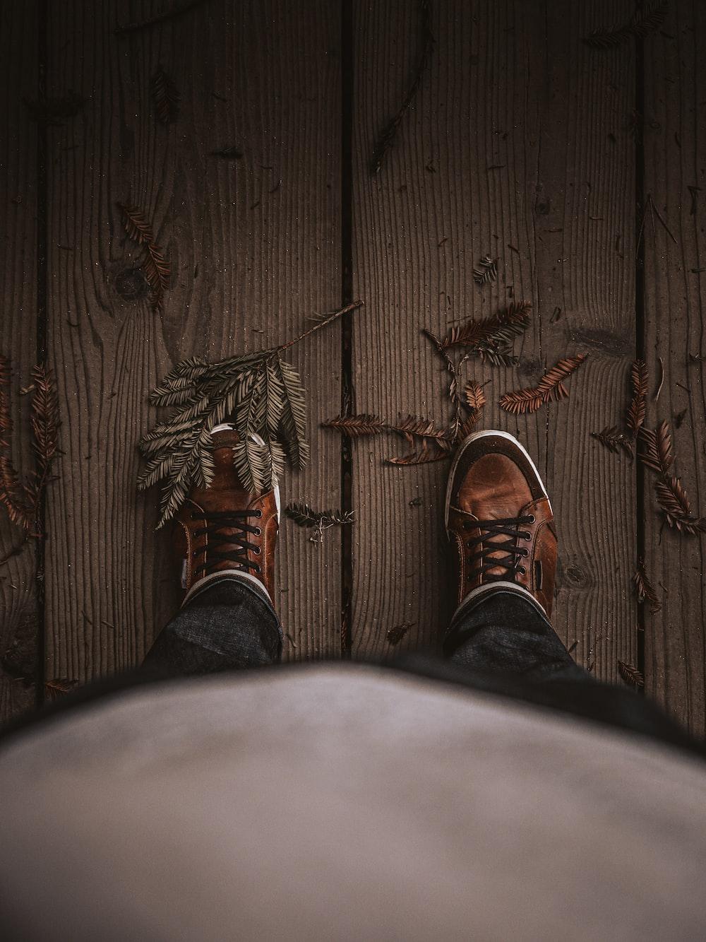 osoba w czarnych spodniach i brązowych skórzanych butach