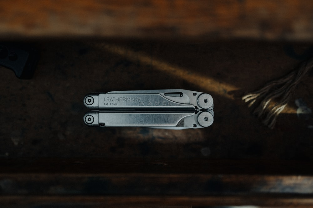 silver multi tool on brown wooden table