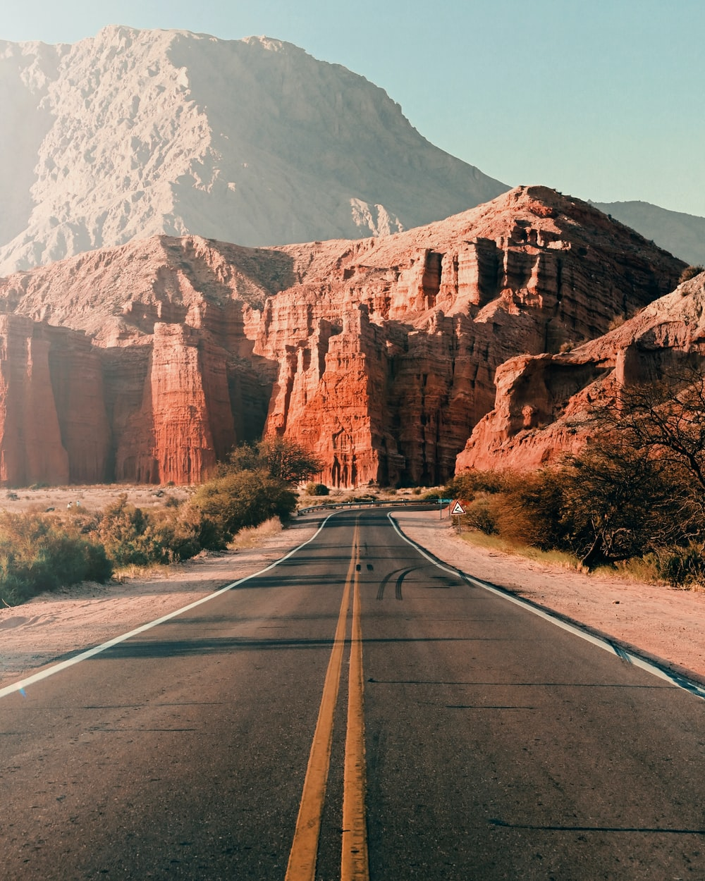 gray asphalt road near brown mountain during daytime