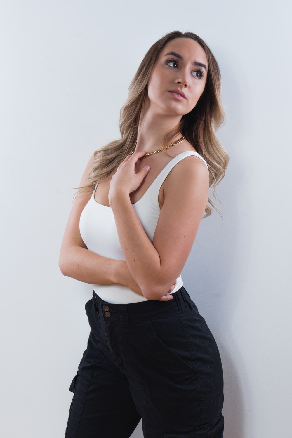 woman in white tank top and blue denim bottoms