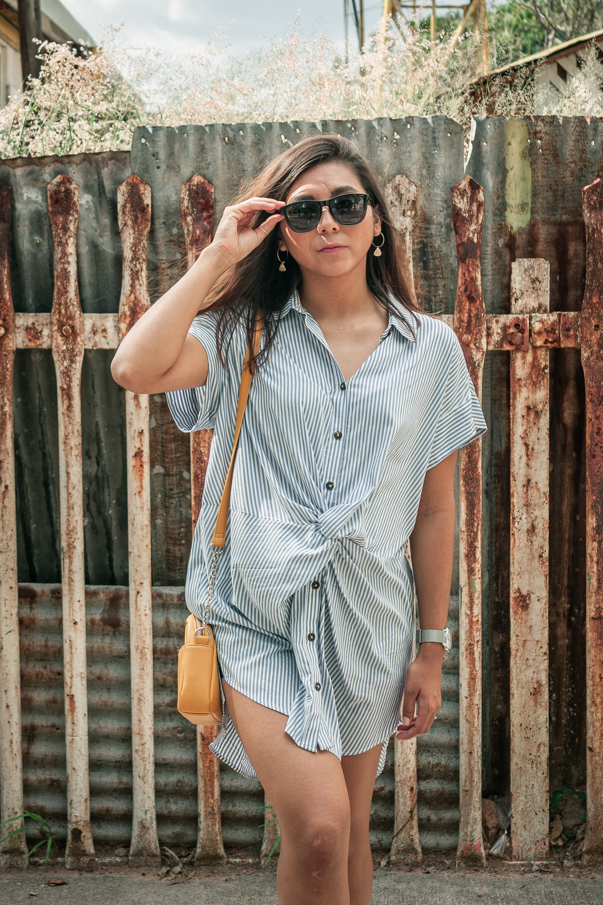 woman in white and blue stripe button up shirt wearing black sunglasses