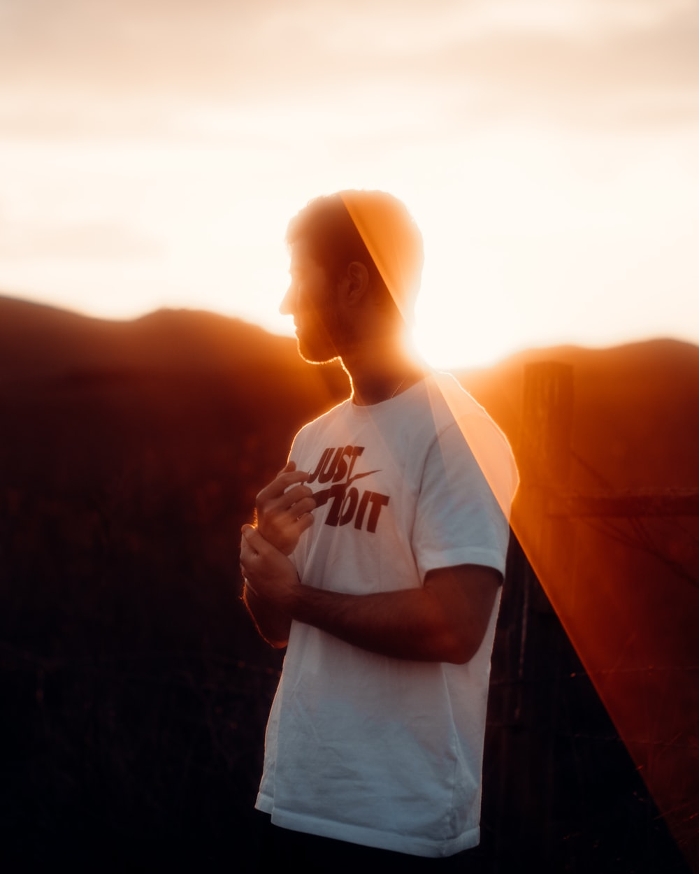 man in white crew neck t-shirt standing on top of mountain during sunset