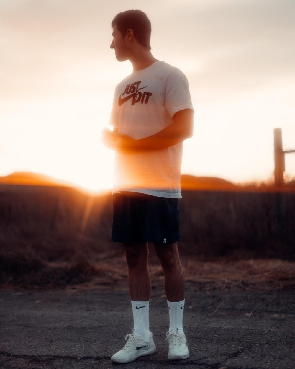 man in white crew neck t-shirt and black shorts standing on brown field during sunset