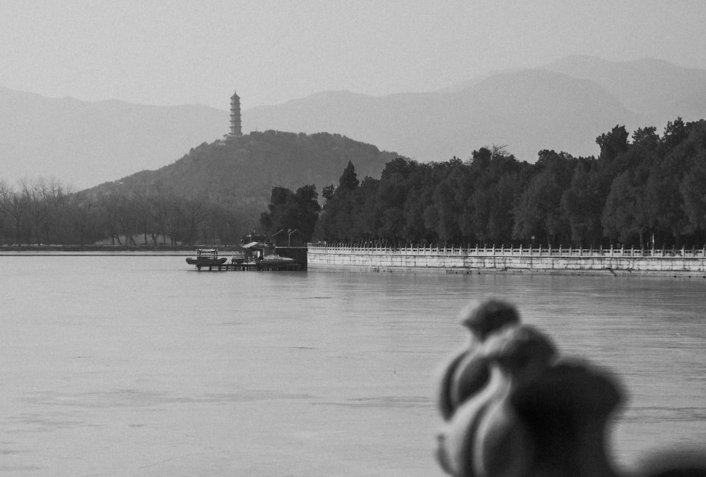 grayscale photo of people sitting on dock