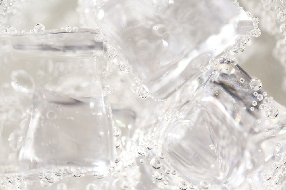 clear glass container on white textile