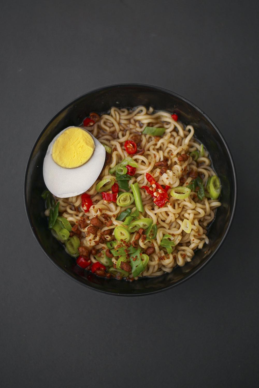noodles with sliced lemon on black ceramic bowl