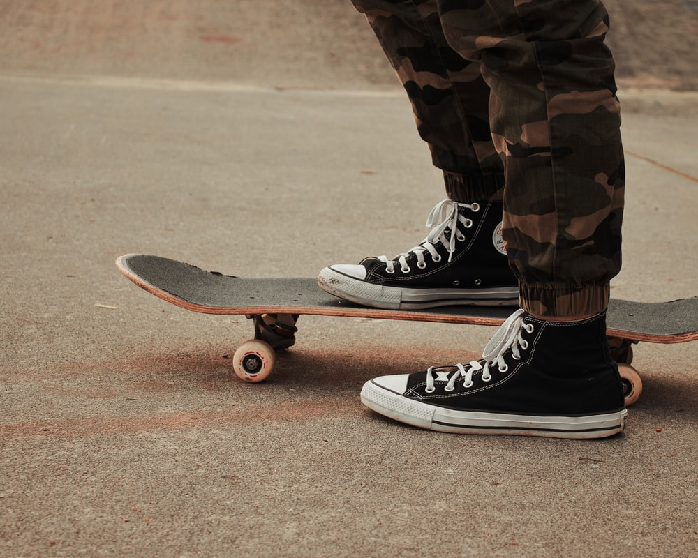 person in black and white nike sneakers riding skateboard during daytime