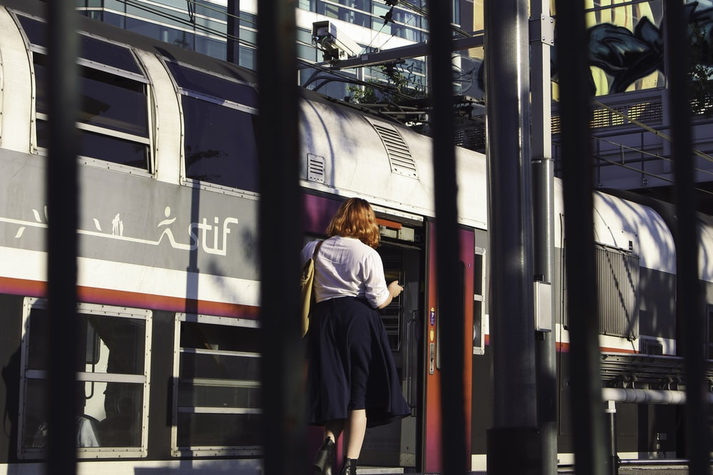 man in black jacket standing beside red and black train during daytime