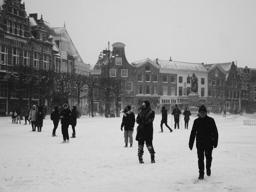 people walking on snow covered ground near building during daytime