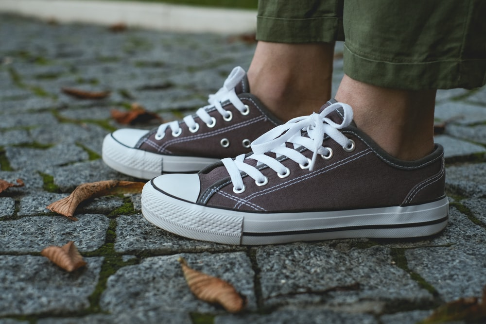 person wearing gray and white converse all star high top sneakers