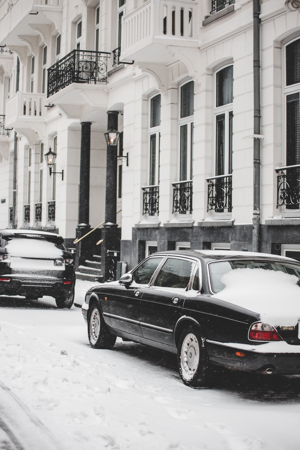 black sedan on road covered with snow during daytime