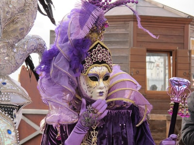 person wearing gold and purple mask mardi gras zoom background