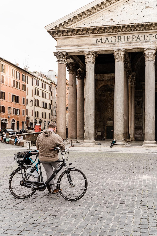 man in gray jacket riding bicycle on street during daytime