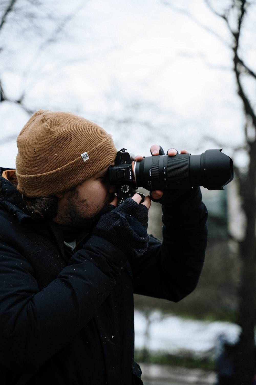 man in black jacket and brown knit cap using black dslr camera